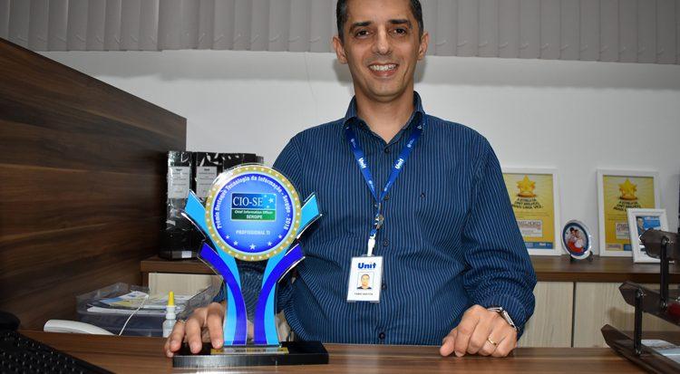 O professor Fábio e o troféu que  destaca o profissional  da tecnologia da informação 2018